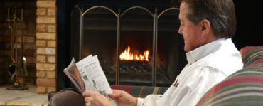 Man reading newspaper near fireplace