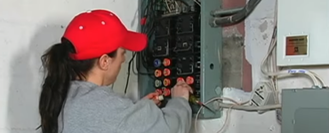 Electrician working on a circuit breaker