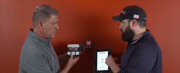 Pete and garage door specialist looking at garage door opener and phone app