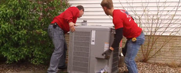 Two workers installing a new A/C unit outdoors