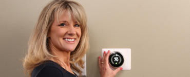 Megan standing next to a thermostat