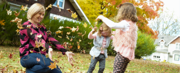 Mom and daughters playing in leaves
